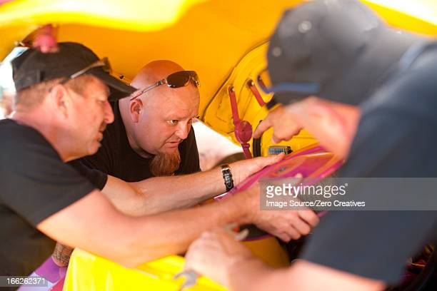 Mechanics working on colorful car