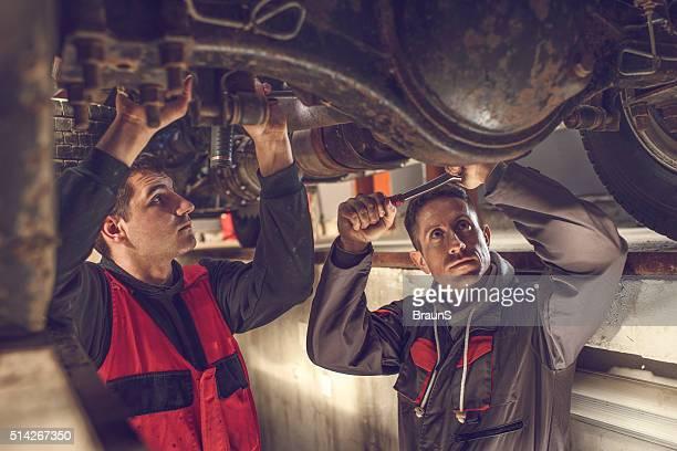 Mechanik arbeiten zusammen an einem Gehäuse für ein Auto.