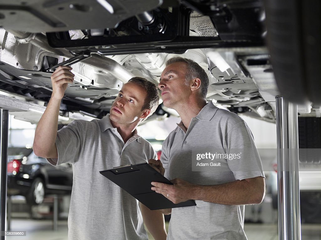 Mechanics working underneath car : Stock Photo