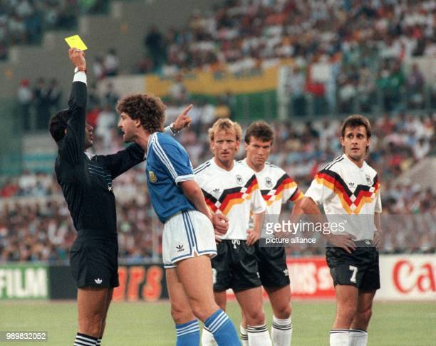 Mecian referee Edgardo Mendez shows Argentinean player Gustavo Dezotti the yellow card after a foul against his German opponent Pierre Littbarski...