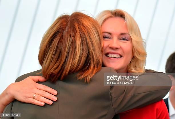 Mecklenburg-Western Pomerania's state premier Manuela Schwesig is hugged by Rhineland-Palatinate's state premier Malu Dreyer, interim leader of...