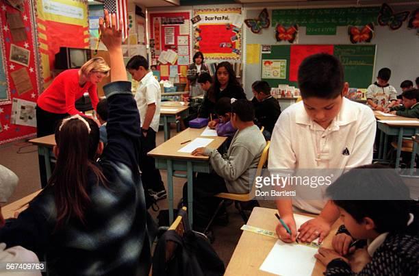 MEClassHelperDB010798––SantaAna–– Fremont Elementary School fifth–grade teacher Lisa Haydt helps a student at his desk another girl waves her hand...