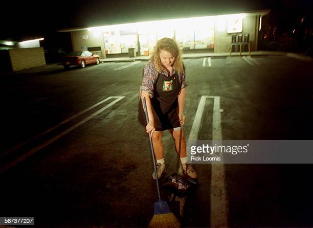 MEClerk#30825RL–KODAK G–Angela Mitchell e sweeps the parking lot in the early morning hours of an overnight shift at an Orange County 7–Eleven