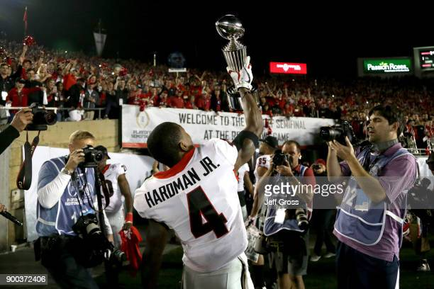 Mecole Hardman of the Georgia Bulldogs celebrates by holding up the trophy after the Georgia Bulldogs beat the Oklahoma Sooners in the 2018 College...