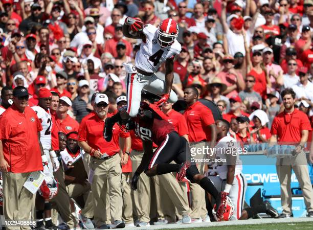 Mecole Hardman of the Georgia Bulldogs jumps over JT Ibe of the South Carolina Gamecocks during their game at WilliamsBrice Stadium on September 8...