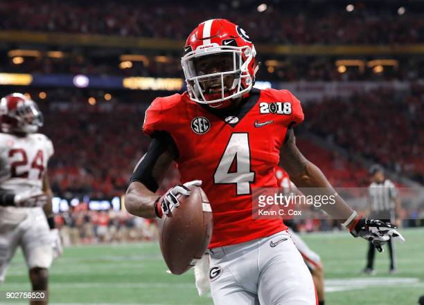 Mecole Hardman of the Georgia Bulldogs runs one yard for a touchdown during the second quarter against the Alabama Crimson Tide in the CFP National...