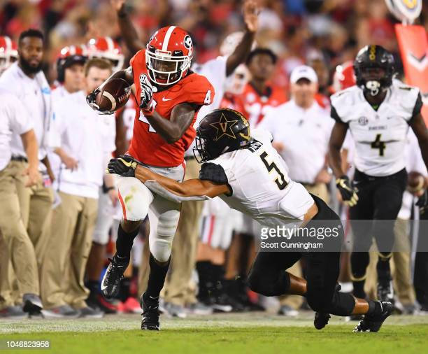 Mecole Hardman of the Georgia Bulldogs runs with a catch against LaDarius Wiley of the Vanderbilt Commodores on October 6 2018 at Sanford Stadium in...
