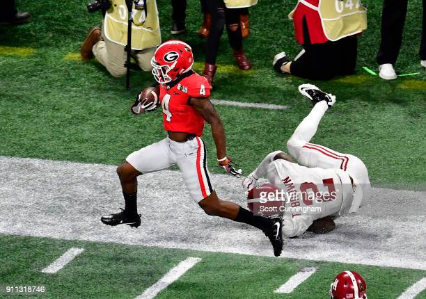 Mecole Hardman of the Georgia Bulldogs runs with a catch for a touchdown against Tony Brown of the Alabama Crimson Tide in the CFP National...
