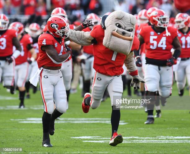 Mecole Hardman of the Georgia Bulldogs takes the field with team mascot Hairy Dog before the game against the Massachusetts Minutemen on November 17...