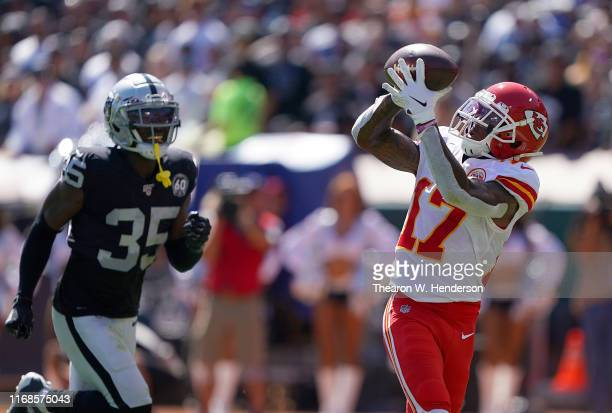 Mecole Hardman of the Kansas City Chiefs catches a touchdown pass over Curtis Riley of the Oakland Raiders during the second quarter of an NFL...