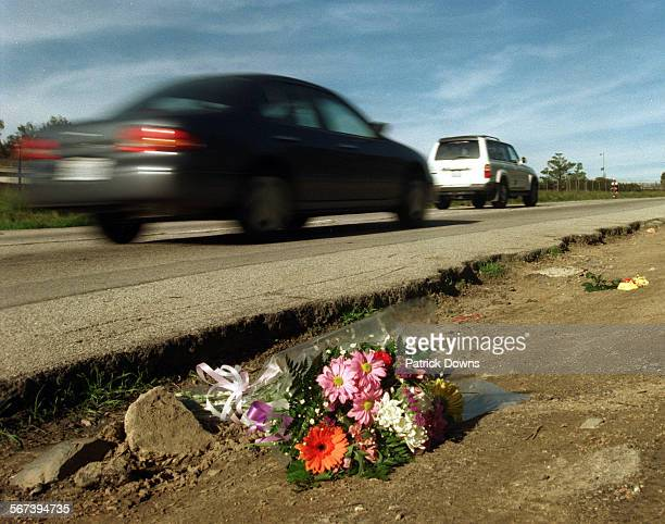 flowers lie by the side of the road on Skirball Center Dr as cars whiz by placed there in memory of Ennis Cosby The son of comedian Bill Cosby was...
