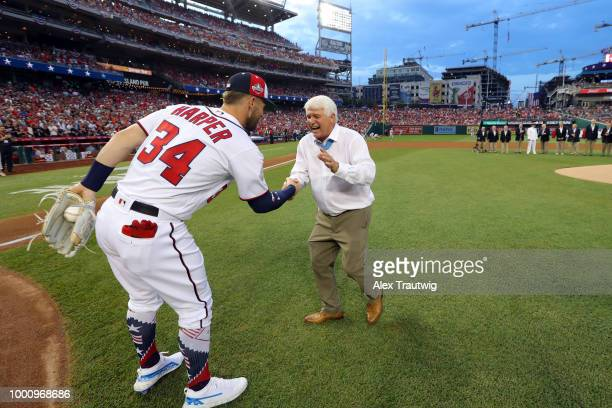 Medal of Honor recipient James McCloughan shakes hands with Bryce Harper of the Washington Nationals after throwing the ceremonial first pitch prior...