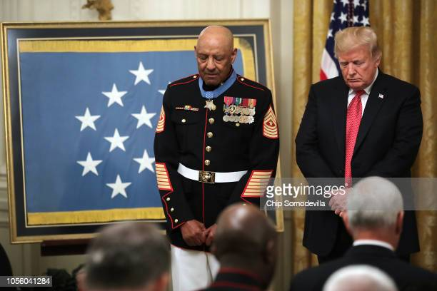 Medal of Honor recipient retired Marine Sgt Major John L Canley and US President Donald Trump bow their heads in prayer during a ceremony in the East...