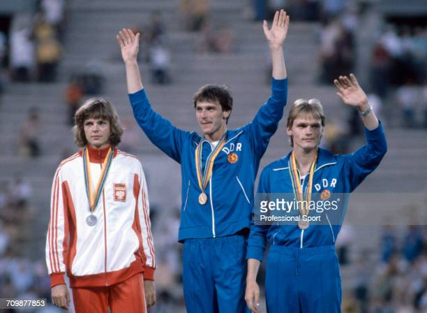 Medal winners from the Men's high jump event at the 1980 Summer Olympics stand and wave on the medal podium with gold medallist Gerd Wessig of East...