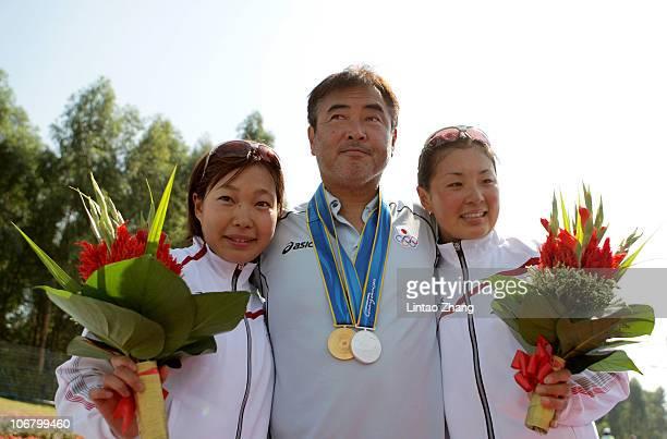 Medal winners Mariko Adachi and Akane Tsuchihashi of Japan pose with their coach Kenjiro Iijima after receiving the medals won in the Women's...
