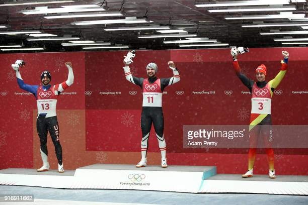 Medalists Chris Mazdzer of the United States David Gleirscher of Austria and Johannes Ludwig of Germany celebrate at the flower ceremony following...