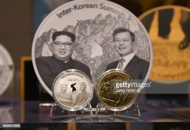 Medallions commemorating the historic interKorean summit between Moon Jaein and Kim Jong Un are displayed during an unveiling ceremony at a sales...