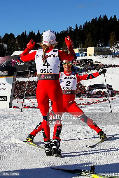 Medallists Therese Johaug of Norway and Marit Bjoergen of Norway celebrate after crossing the finish line in the Ladies Cross Country 30km Mass Start...