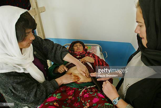 Medecins du Monde midwife Priscille Saureprain from France examines Razagul who is 4 months pregnant and suffering from a hernia at the Chagcharan...