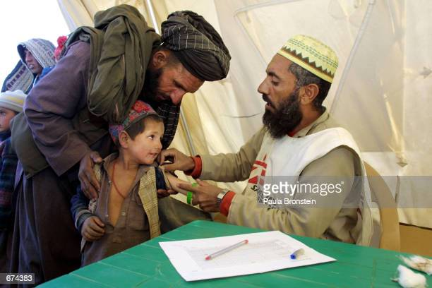 Medecins Sans Frontieres worker examines an Afghan refugee child November 29 2001 at the Chaman refugee camp on the Pakistani border with Afghanistan
