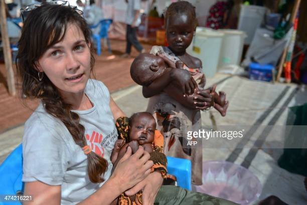 A Medecins Sans Frontieres worker holds a South Sudanese baby while two little girls wait for treatment at the MSF hospital in Juba on February 22...