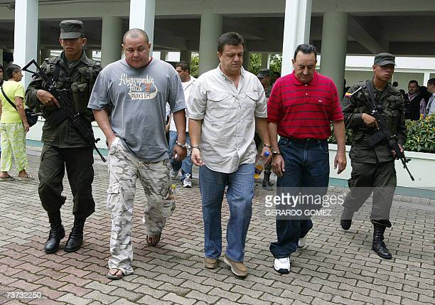 Colombian police officers escort three of seven men arrested for allegedly trafficking heroine into the Unites States on March 28th in Medellin...