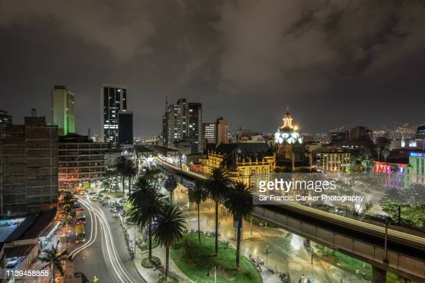 medellin skyline illuminated at night with blurred lights of elevated metro and traffic lights in antioquia, colombia - medellin colombia fotografías e imágenes de stock