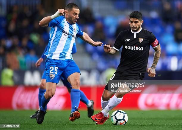 Medhi Lacen of Malaga CF competes for the ball with Ever Banega of Sevilla FC during the La Liga match between Malaga and Sevilla at Estadio La...