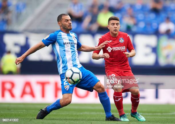 Medhi Lacen of Malaga CF duels for the ball with Francisco Portillo of Getafe CF during the La Liga match between Malaga CF and Getafe CF at Estadio...