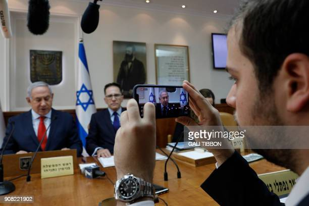 A media advisor of Israeli Prime Minister Benjamin Netanyahu makes a facebook live broadcast as he opens the weekly cabinet meeting at his Jerusalem...