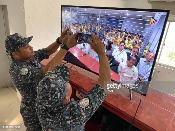 Media and jail personnel take photos from a TV screen of the trial proceedings which only the government owned media has been granted to cover on...