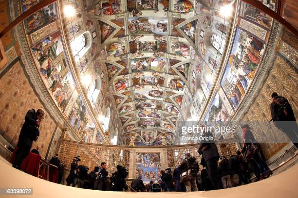 Media arrive as clergy and workers make arrangements in the Sistine Chapel before the papal conclave on March 9 2013 in Vatican City Vatican...
