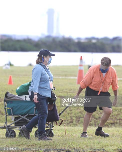 A media broadcast crew arrives to make preparations for launch coverage at the Kennedy Space Center in Florida on May 26 2020 Looming in the distance...