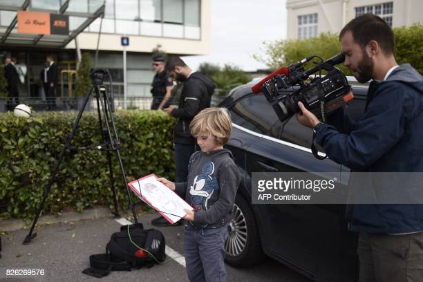 Media cameraman films a sketch of Brazilian superstar Neymar made by a boy, as they wait for Neymar's arrival from Barcelona outside the business...