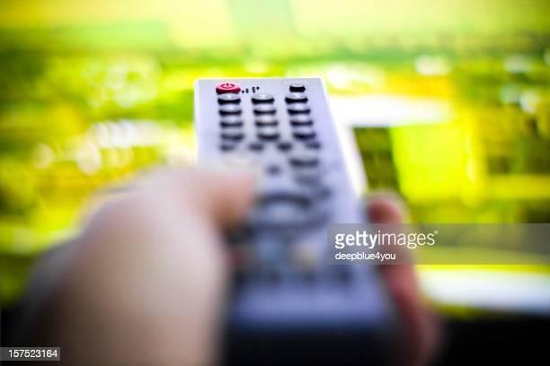 Media cencept - hand holding remote tv background