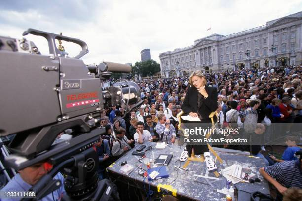 Media correspondent reporting from a temporary stage surrounded by crowds gathering outside Buckingham Palace following the death of Diana, Princess...