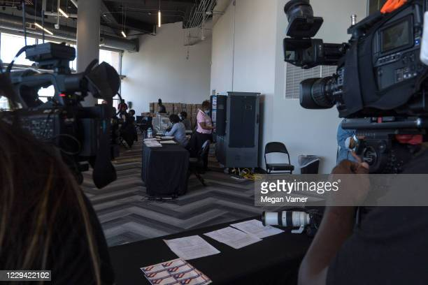 Media crews film while an election worker processes absentee ballots at State Farm Arena on November 2, 2020 in Atlanta, Georgia. With...
