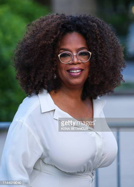 US media executive and talk show host Oprah Winfrey waves as she arrives to the opening celebration of the Statue of Liberty Museum on Liberty Island...