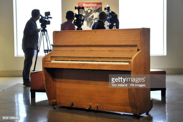 Media film behind the Challen upright piano from Abbey Road Studios played by the Beatles and Pink Floyd at the auction house in London which is...