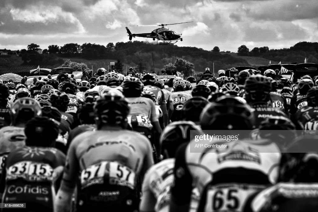A media helicopter flies over the pack riding during the 178 km tenth stage of the 104th edition of the Tour de France cycling race on July 11, 2017 between Perigueux and Bergerac. /