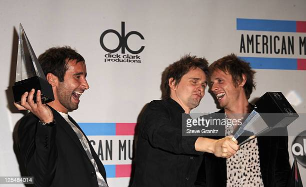 Media manager Tom Kirk with musicians Matthew Bellamy and Dominic Howard of the band Muse pose in the press room at the 2010 American Music Awards...