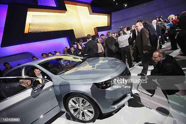 Media members and enthusiasts inspect the newly unveiled 2014 Chevrolet Impala at the New York International Auto Show at the Jacob Javits Convention...