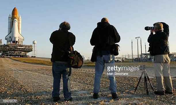 Media members photograph Space Shuttle Discovery as it rolls to launch pad 39b atop the crawler transporter in preparation for its planned December...