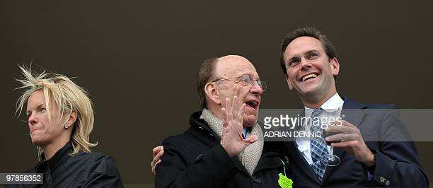 Media mogul Rupert Murdoch stands beside his son James Murdoch and daughter Elisabeth Murdoch on a balcony overlooking the racing during the third...