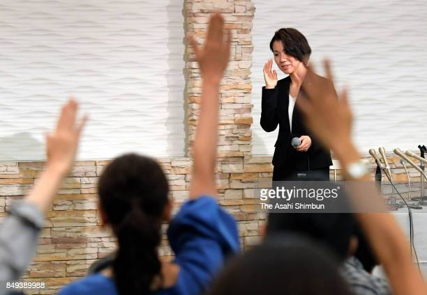 Media reporters raise their hands to ask questions to lower house lawmaker Mayuko Toyota during a press conference after the meeting with her...