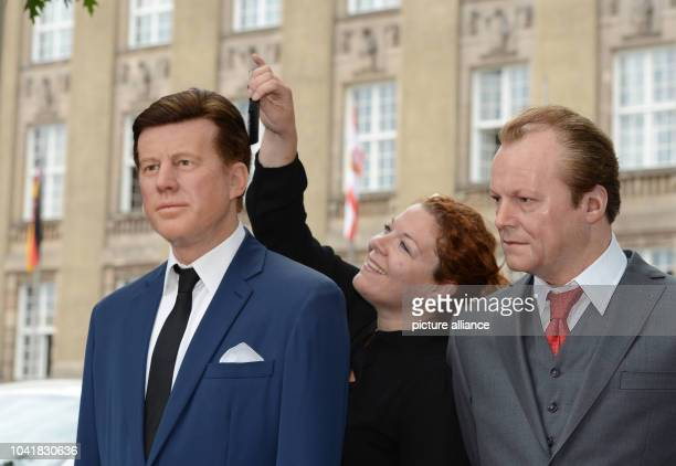 Media representative Nina Zerbe works on the Madame Tussaud's wax figures of former US President John F Kennedy and former German Chancellor Willy...