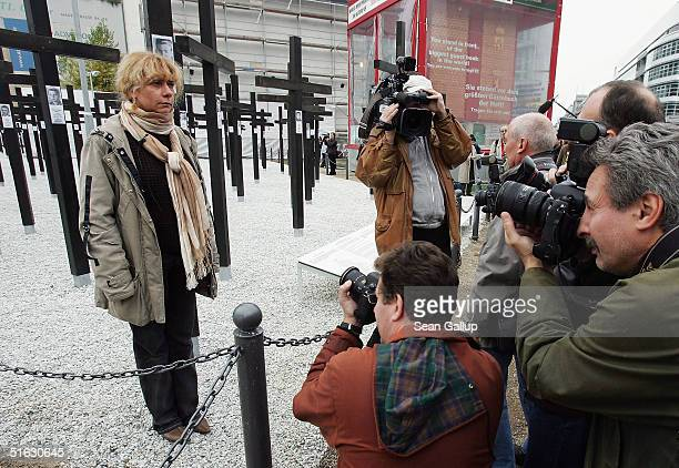 Media representatives photograph Alexandra Hidebrandt as she attends the unveiling of the memorial to victims of the Berlin Wall she commissioned on...