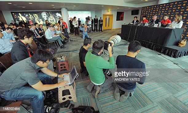 Media take pictures of Manchester United's new signings English midfielder Nick Powell and Japanese midfielder Shinji Kagawa as they attend a press...