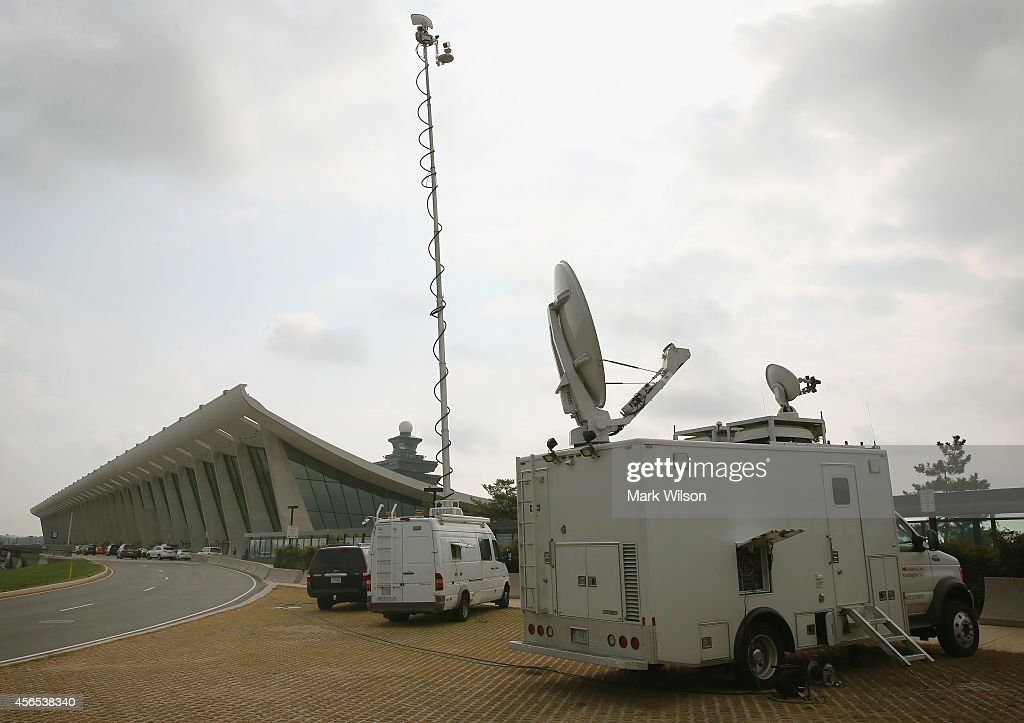 Media trucks are parked in front of the main terminal at Washington Dulles International Airport October 2, 2014 in Dulles, Virginia. The Center for Disease Control CDC announced that Ebola patient being treated at theTexas Presbyterian hospital passed through Washington Dulles airport on a United Airlines flight two weeks ago.