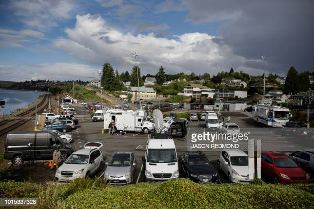 Media trucks are pictured in a parking lot at the Steilacoom Ferry dock which takes investigators to Ketron Island the crash site of the Horizon Air...